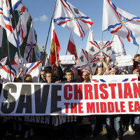 Assyrian Christians, who had fled Syria and Iraq, carry placards and wave Assyrian flags during a gathering in late May in front of U.N. headquarters in Beirut. (CNS photo/Nabil Mounzer, EPA) See CHRISTIAN-PERSECUTION-CONFERENCE Dec. 11, 2015.